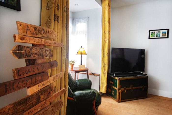 An elegant sitting room with white walls is shown, with a green leather armchair in the window with a reading table, a flat screen tv on a battered suitcase and there's a wooden sign post to show where to find Hogsmeade and other magical locations.