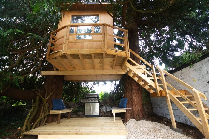A tree house is over an outdoor grill area in a garden.