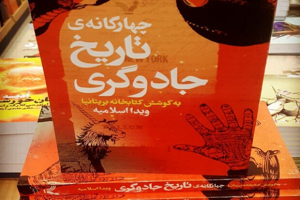 The red and orange cover of the Persian edition of Harry Potter A History of Magic is pictured, some copies stacked on each other at a bookstore.
