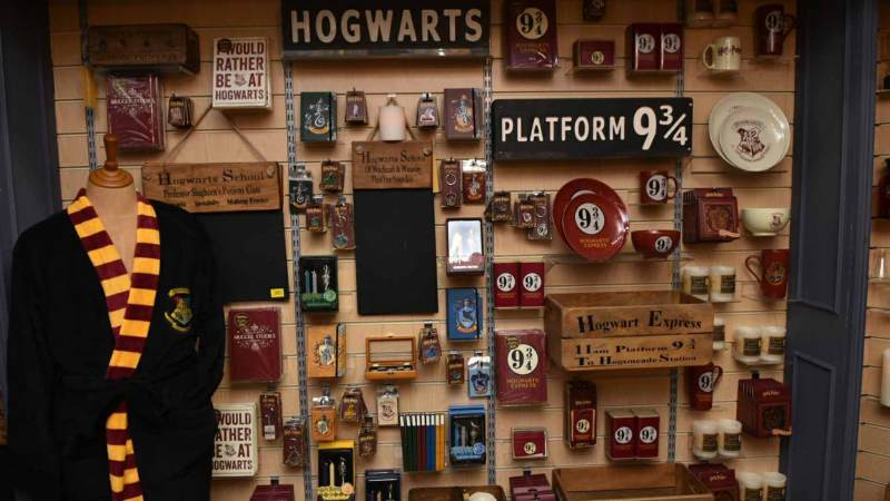 There is a shop wall full of cool Harry Potter items such as plates, signposts, and keychains.