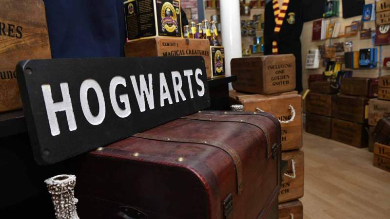 A small Harry Potter shop has a wall full of smaller collectible items, and there are crates and boxes and a Hogwarts sign.