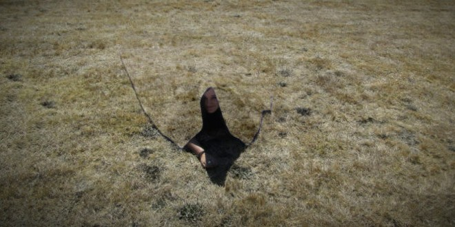A woman's head is visible under a blanket that blends into the grass she's lying on.