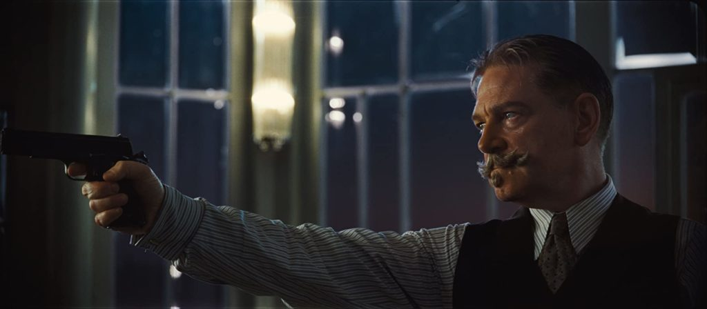 "Sir Kenneth Branagh brandishes a gun as Hercule Poirot in ""Death on the Nile""."