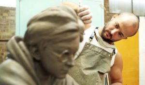 Image of a man sculpting the face of A statue of Harry Potter.
