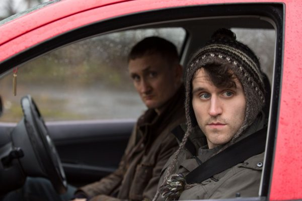 """Harry Melling peers out the window of a vehicle in a film still from """"Say Your Prayers""""."""