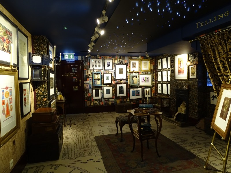 MinaLima's gallery is a spacious basement area, dark and full of prints framed on the walls.