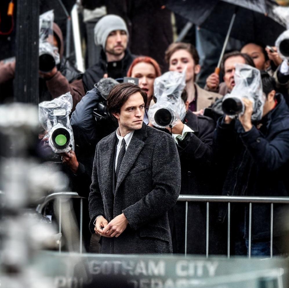 "Robert Pattinson faces the paparazzi as Bruce Wayne during filming for ""The Batman""."