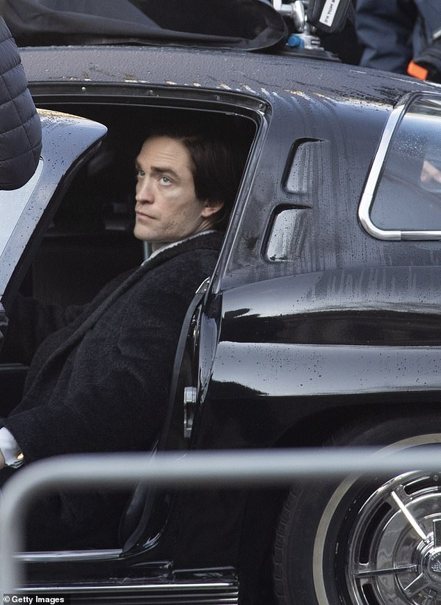 """Robert Pattinson climbs into the back of a car as Bruce Wayne during filming for """"The Batman""""."""