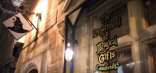 An old stone building has a shopfront for the Department of Magical Gifts, and there is an antique looking shop label and a street light or candelabra.