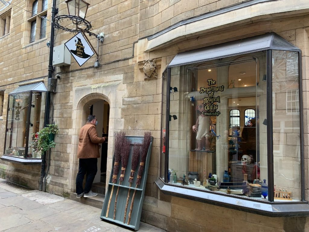 A pretty, pale stone buildin has a bay window shop front and broomsticks, and antique candelabra. The label on the window of the magical merch shop says The Department of Magical Gifts.
