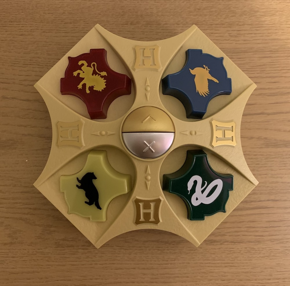 The Harry Potter Wizarding Quiz game device has four Hogwarts House crest buttons and two answer buttons, silver for false and gold for true.
