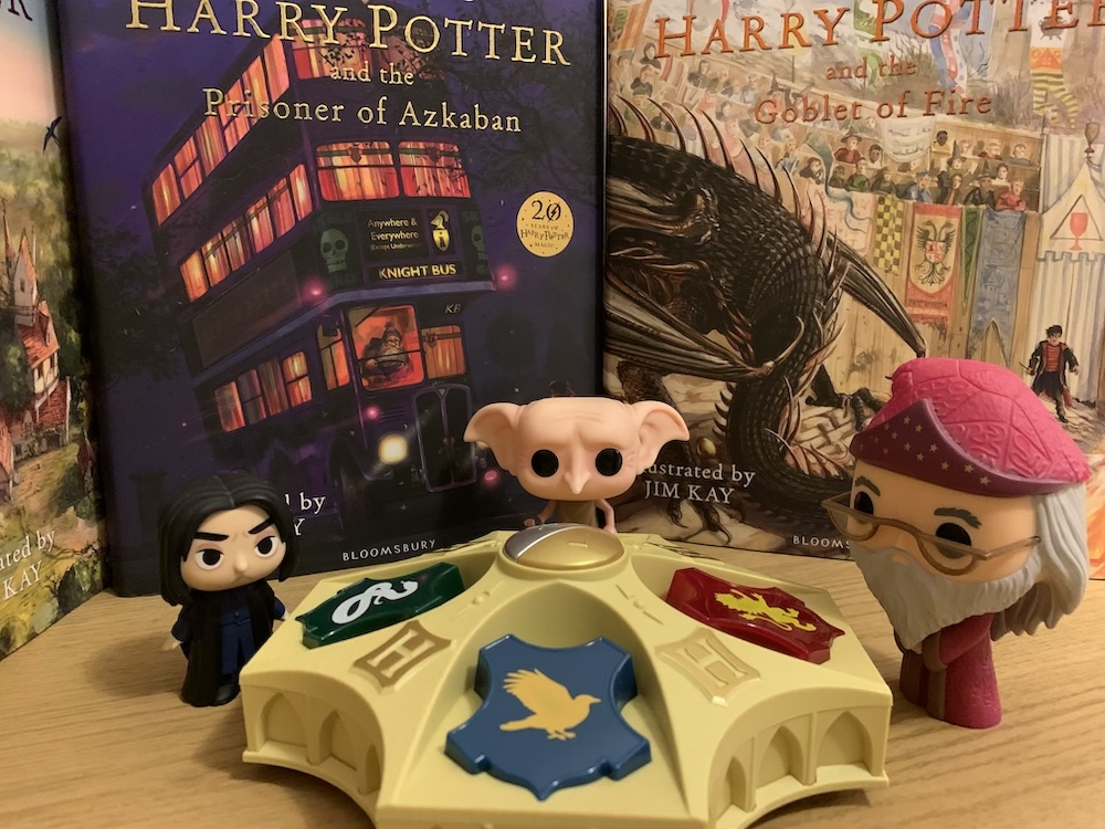 "Funko Pop! figures of Dumbledore, Dobby, and Snape are posed with the Harry Potter Wizarding Quiz game in front of illustrated editions of ""Harry Potter""."