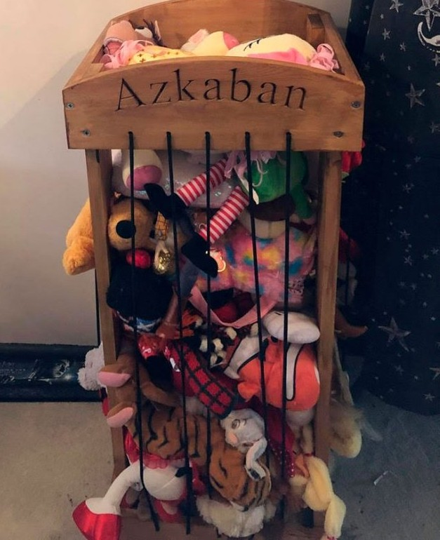 There is a toy cage with a bunch of stuffed toys that says Azkaban on the top board.