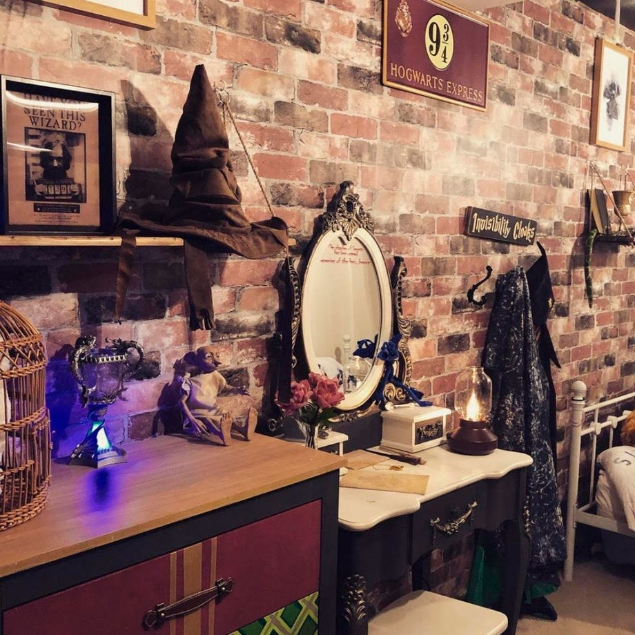 A small bedroom has brick wallpaper, Platform 9 and 3/4 signs, a sorting hat and other items on a dresser and a child-sized vanity table.
