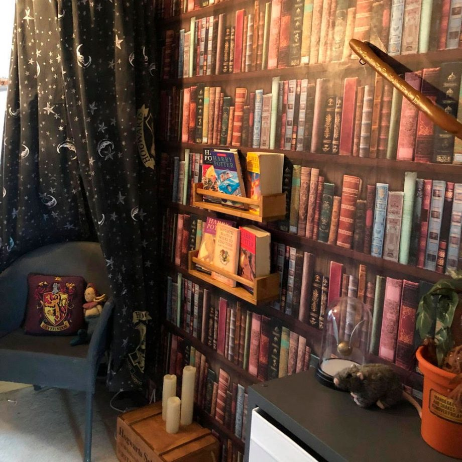 A small bedroom has a bookshelf wallpaper and a reading nook with the Harry Potter books on a real shelf.
