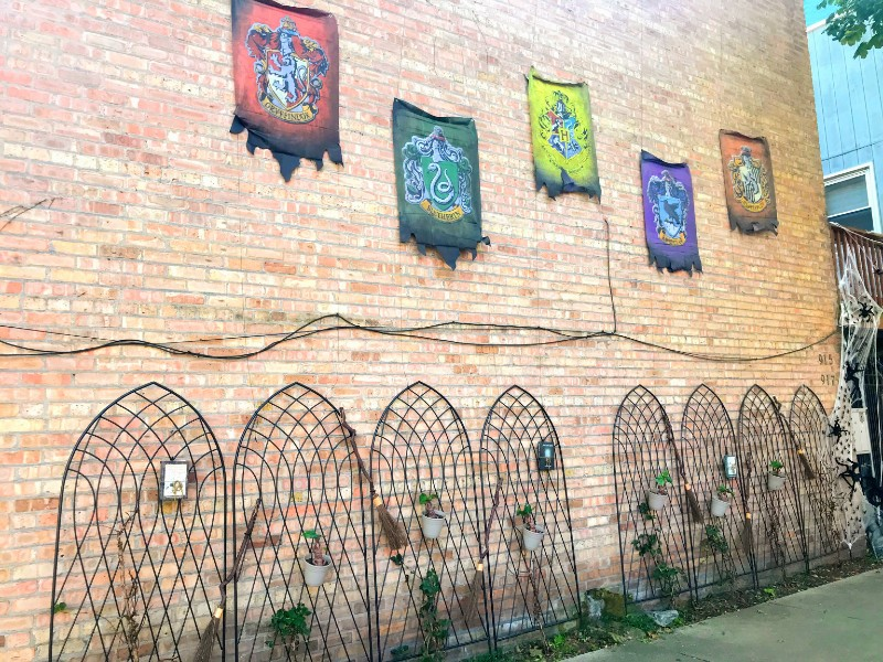 A brick wall has banners of Hogwarts and the houses and a decorative fence with broomsticks and Harry Potter schoolbooks pinned on it.