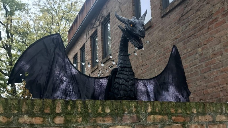 An animatronic dragon peeks out majestically from a residential house's brick fence.
