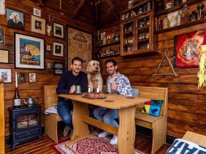 Dan Harrison and Mark Parkinson are sitting in their Leaky Cauldron summerhouse with their dog.