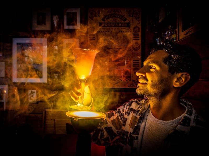 Owner of Leeds Leaky Cauldron summerhouse holds a glowing orange potion in the dark.