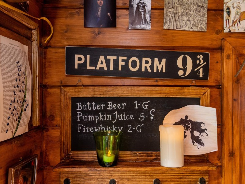 A cute Platform 9 and 3/4 sign is on a summerhouse's wood-panelled wall with prices for butterbeer, pumpkin juice and firewhiskey.