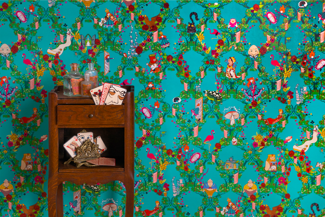 "This MinaLima ""Alice's Adventures in Wonderland"" wallpaper features many of Lewis Carroll's characters sitting in a pattern of red and white rose bushes on a light blue background."