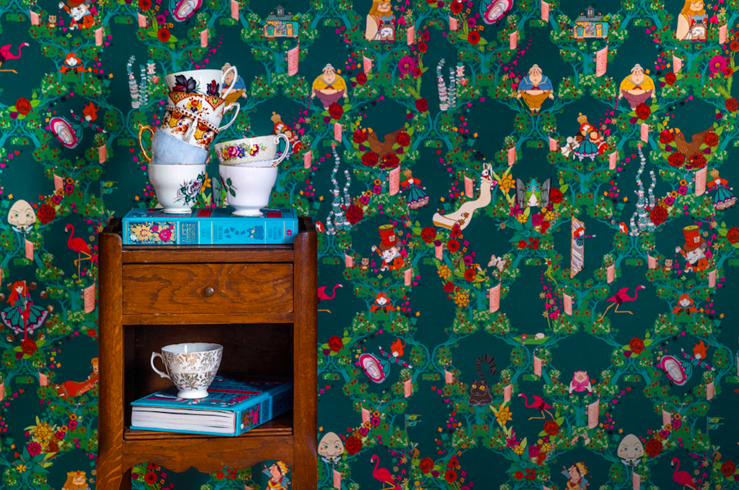 "Colorful teacups and books sit in front of the MinaLima dark blue version of the ""Alice's Adventures in Wonderland"" wallpaper."
