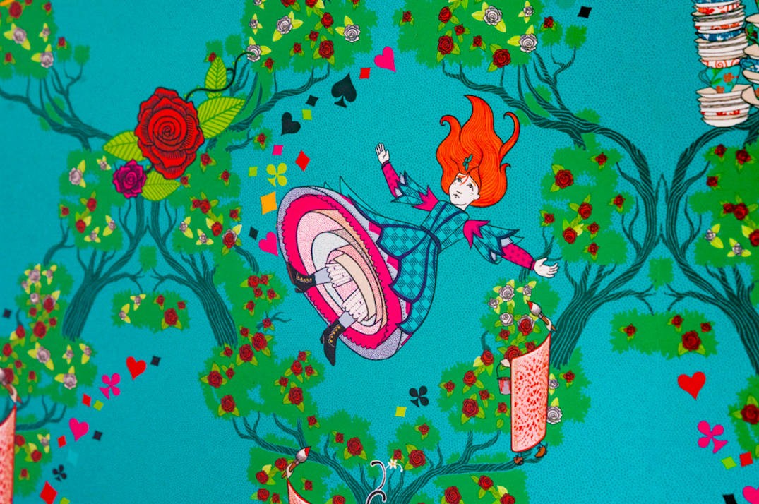 "This MinaLima ""Alice's Adventures in Wonderland"" wallpaper features Alice as she falls through the rabbit hole to Wonderland surrounded by white and red roses on a light blue background."