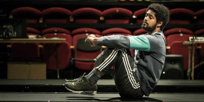 Alfie Enoch is sitting on a stage in casual clothes, in character.