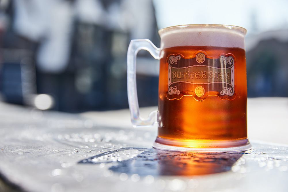 A plastic tankard of butterbeer sits on a wall in the sunshine in Hogsmeade at The Wizarding World of Harry Potter at Universal Studios Hollywood.