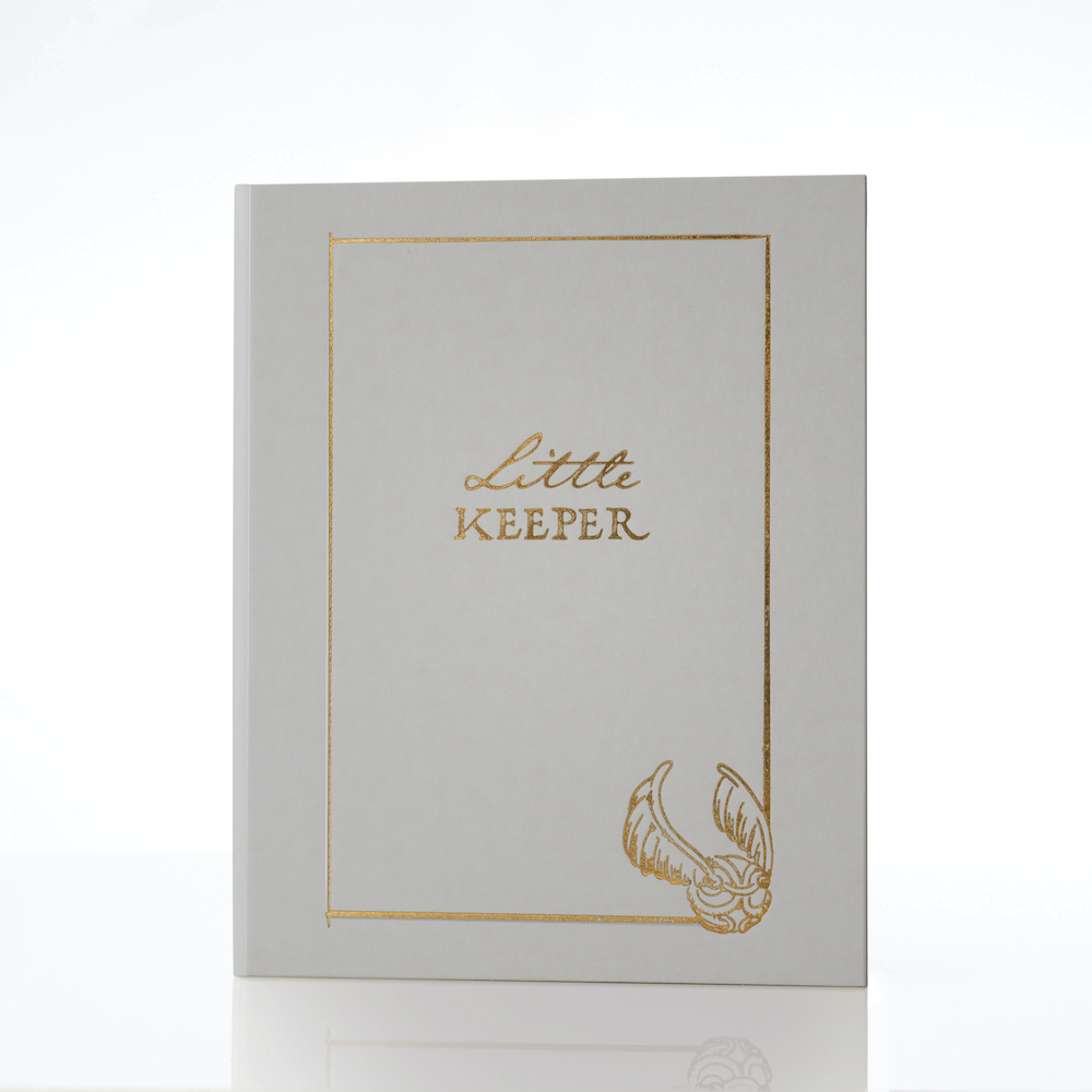 "The ""Harry Potter"" Little Keeper Baby Album is covered in gray linen with gold embellishments."