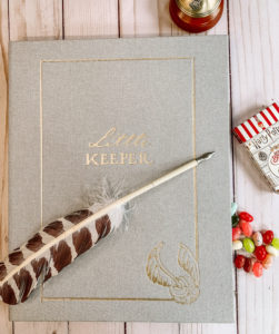 "An image of the front cover of the ""Harry Potter"" Little Keeper Baby Album, which is covered in grey linen with gold embellishments and a quill lying across it."