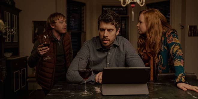 """In a still from Season 2 of """"Servant"""", Rupert Grint (who plays Julian Pearce) waves a wine glass in mid-discussion with Toby Kebbel (who plays Sean Turner) and Lauren Ambrose (who plays Dorothy Turner)."""