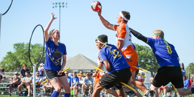 A chaser in an orange jersey is shown attempting to throw the quaffle through the hoops. Three players in blue jerseys are attempting to stop the chaser.