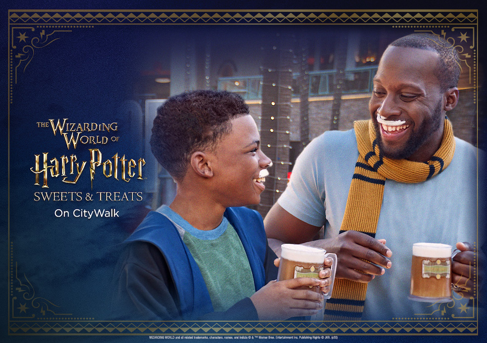 """A young boy in wizards' robes laughs with a man wearing a Hufflepuff scarf, both are holding cups of Butterbeer and have Butterbeer foam moustaches. Text on the left of the photo reads """"The Wizarding World of Harry Potter Sweets and Treats on City Walk."""""""