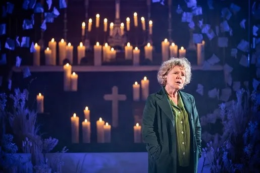 Imelda Staunton recites her lines in front of a backdrop of candles and a cross in a still image from the Donmar Warehouse's holiday production.