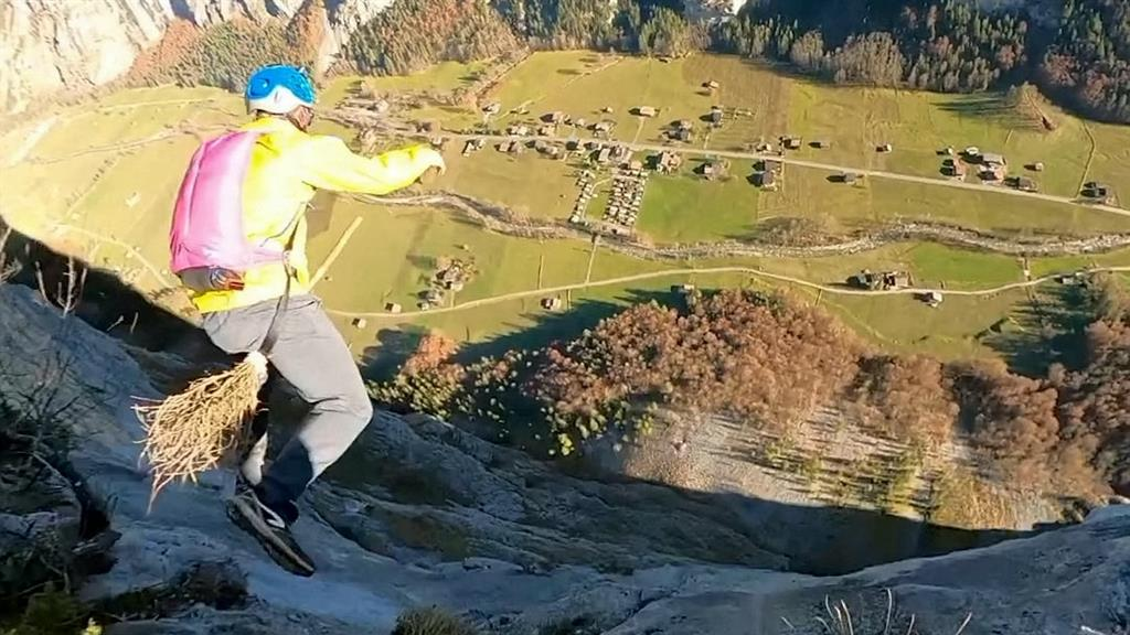 A base jumper in the Swiss Alps appears to be riding a broomstick.