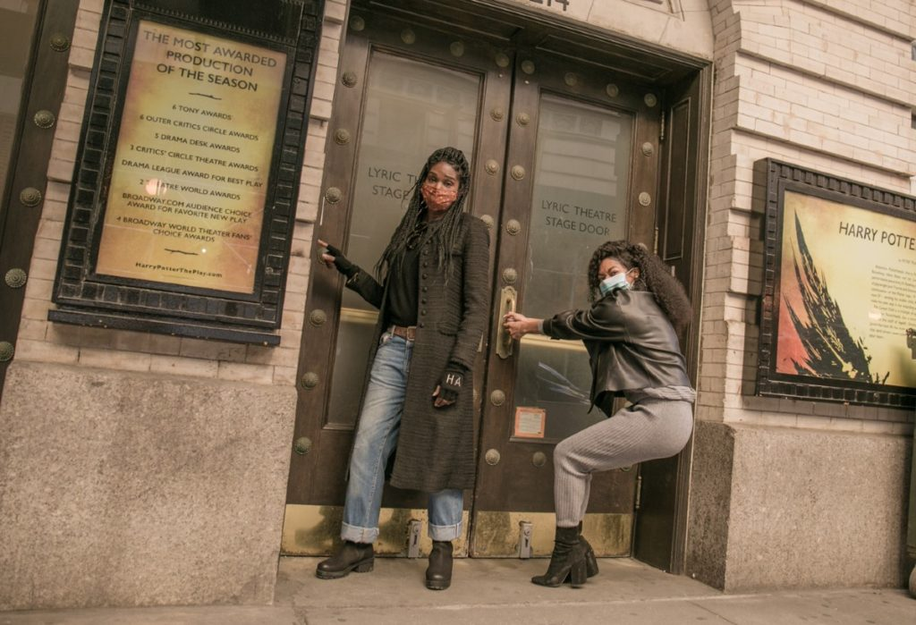 Jenny Jules and Nadia Brown are posing in masks at their Broadway theatre where Cursed Child is. Nadia is jokingly tugging on the door handle.