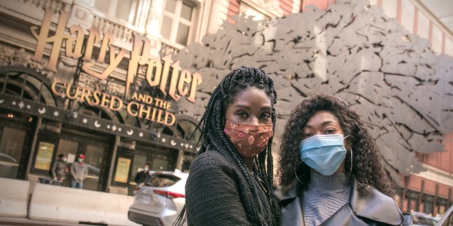 Jenny Jules and Nadia Brown pose in face masks outside the Lyric Theare on Broadway where Harry Potter and the Cursed Child is written over the entrance.