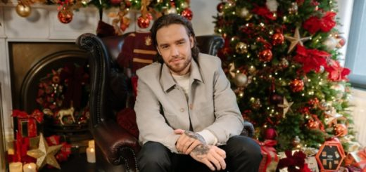 Liam Payne is sitting in front of a richly decorated Christmas tree and a fireplace.