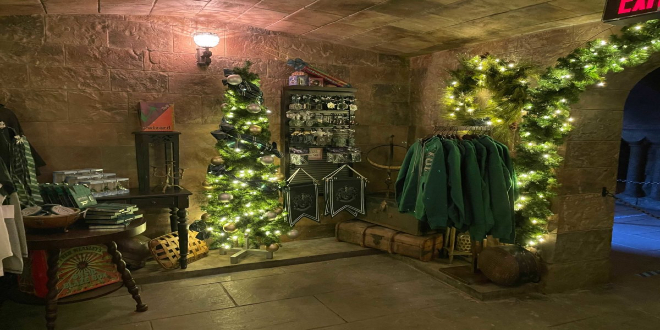 Slytherin's green corner contains clothing, flags, and key rings.