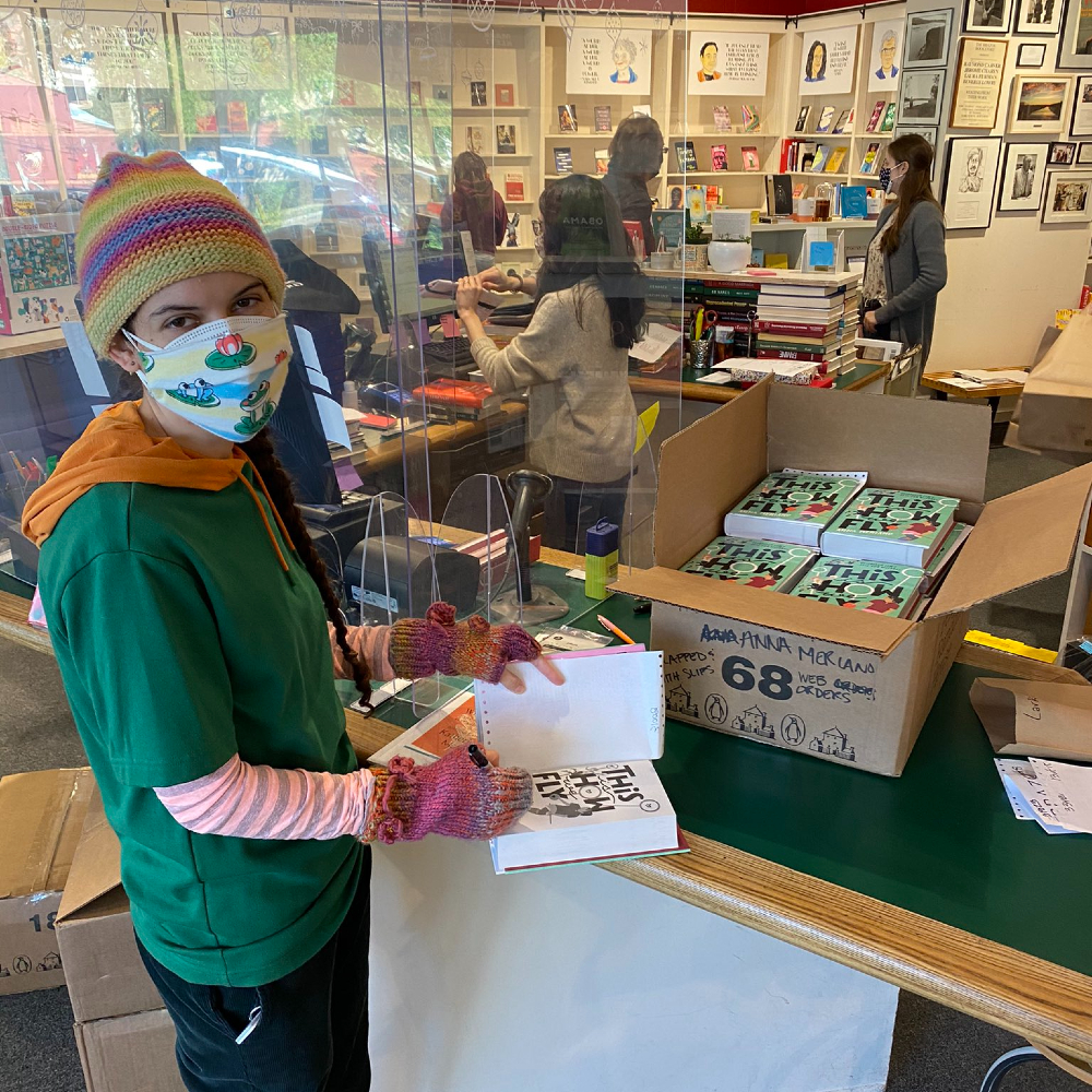 There is woman wearing facemask and signid copies of book This Is How We Fly in bookshop.