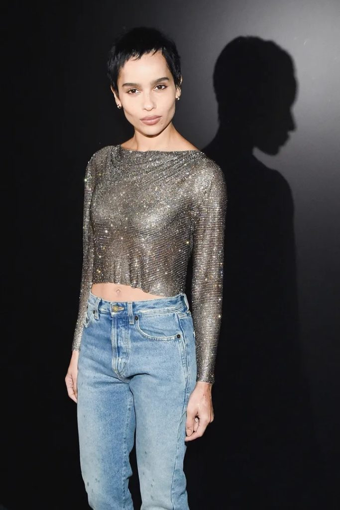 Zoë Kravitz poses in a slinky long-sleeved top and jeans.