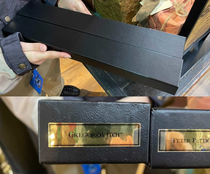 "A shop assistant is holding two long black wand boxes with gilded stickers on the end saying ""Gregorovitch"" and ""Peter Pettigrew"" respectively."