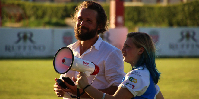 There is a man in white shirt with brown hair and a beard at the left of the image. At the right is a woman in a blue jersey, smaller than the man and holding a megaphone.