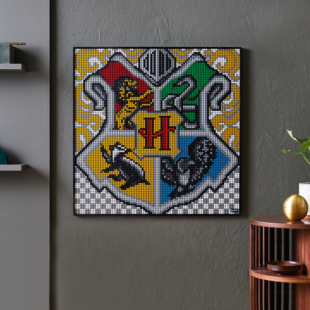 A completed Hogwarts crest, made from four of LEGO's new Harry Potter Hogwarts Crests wall art sets, is hung on a wall.
