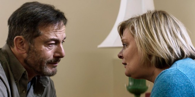 Jason Isaacs is having a strained conversation with his castmate Martha Plimpton. They are sat in a simple room but their expressions are heartbreaking.