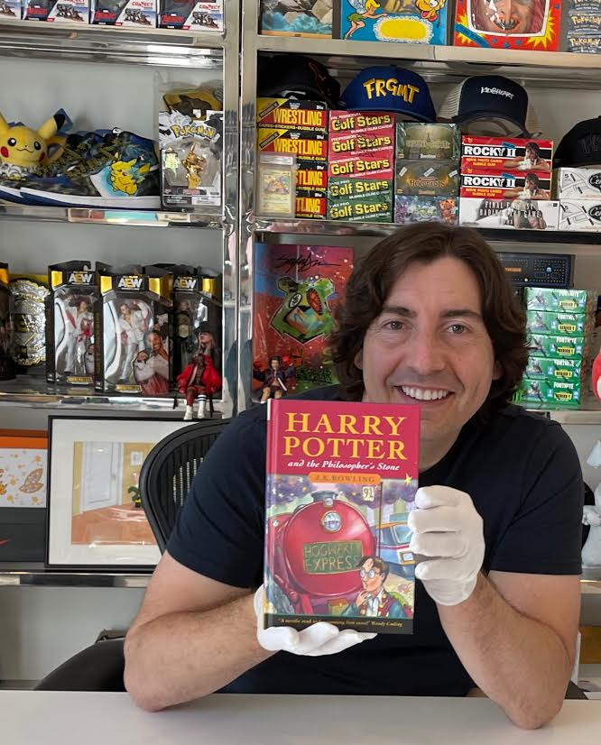 """Jeremy Padawer is shown holding his copy of """"Harry Potter and the Philosopher's Stone"""" with gloved hands."""
