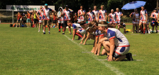 Five players in British jerseys are shown kneeling on the starting line and preparing to run. One of them, a girl on the right, is shouting something. 17 other players are shown in a sub box in the background.