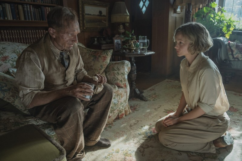 A mud-covered Ralph Fiennes is sitting on a couch and talking with Carey Mulligan, both in costume as archaeologists in The Dig set in the 1940s.