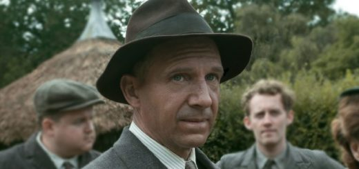 Ralph Fiennes is wearing a brown hat and a 1940s suit and tie as he is in character as working class archeologist Basil Brown.